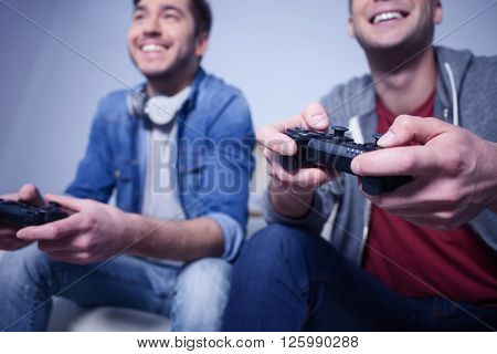 Handsome young men are competing in play station at home. They are sitting and smiling. Focus on their arms holding a game controller