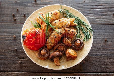 Shish kebab with baked tomato and mushrooms. Spicy shish kebab on wooden table. Homemade supper with fresh vegetables. Top view on grilled meat food