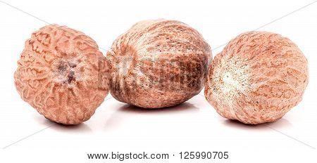 Three nutmeg whole isolated on white background.