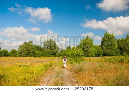 A woman walks along a path through the blooming meadow