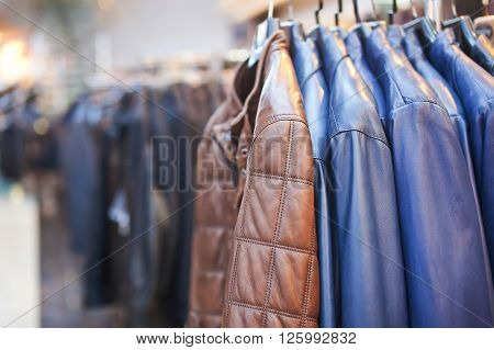 Collection of leather jackets on hangers in the shop.