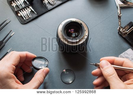 Photo camera lens repair set. Technician engineer check optics alignment and maintenance support of broken photographic 50 1.4 photo camera lens part. Pov to workspace and engineer's hands.