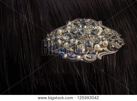 Close view of a fancy diamond brooch with pearls in brunette's hair