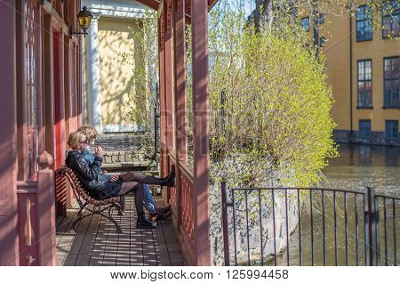 NORRKOPING, SWEDEN - APRIL 19: Young people enjoy sunshine on April 19, 2014 in the industrial landscape of Norrkoping. The historic industrial landscape has become a major tourist attraction.