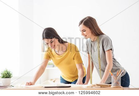 Creative work. Positive smiling beautiful young seamstresses standing at the table and being involved in work while expressing delight