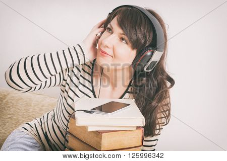 Woman listening an audiobook on smartphone sitting between piles of paper books on the floor