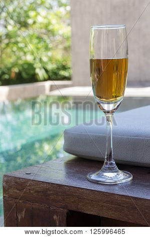 Glass of wine on the bed beside the pool