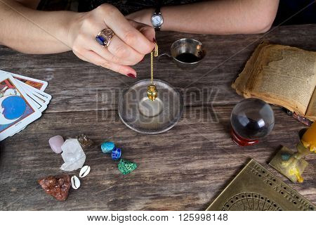Characterization and foretelling with pendulum on wooden table