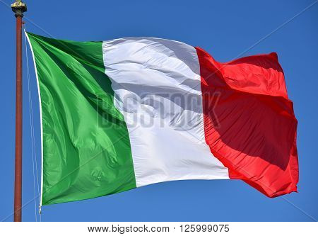 Italian flag fluttering in the wind with blue sky. Green White Red and Azure are Italian national colors.
