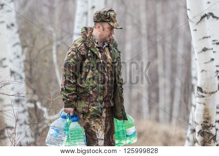 Man in the spring in the woods collecting birch sap