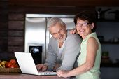 picture of 55-60 years old  - Portrait of a senior couple with a laptop computer - JPG