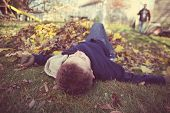 Young boy daydreaming in a pile of fall leaves, slacking on the job, shallow focus poster