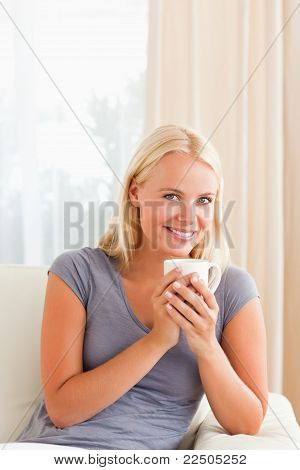 Portrait Of A Woman Sitting On A Couch With A Cup Of Tea