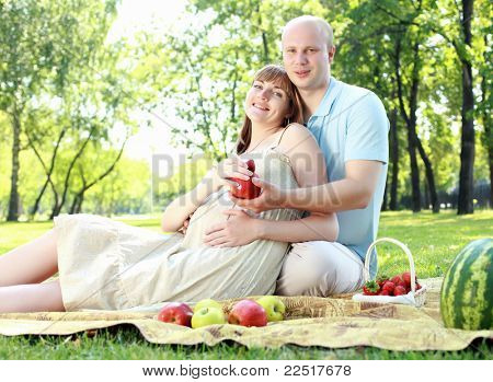 Young couple with a pregnant wife on picnic in the park