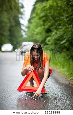 Young female driver wearing a high visibility vest/safety vest, putting in place the warning triangle after her car has broken down