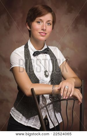 Attractive Red Haired Young Adult Female Portrait Leaning on Chair Against Muslin Background.