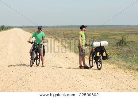 Two Men With Bicycles In Cycling Trip Standing On Road, Sky And Horizon