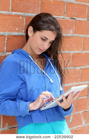 Teenager using electronic tablet in the street