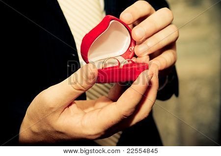 wedding rings in groom's hands