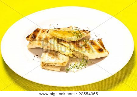 A Grilled Sandwich Of Melting Cheese, On A White Plate