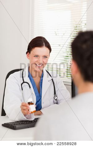 A female doctor is showing pills to a patient in her office