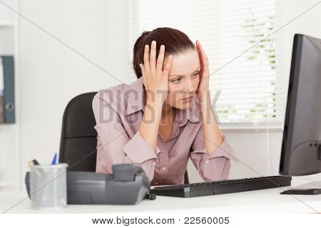 A stressed businesswoman is looking to the screen of her pc in an office