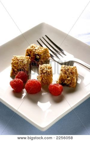 A Plate Of Sliced Up Muesli Bar With A Few Scattered Raspberries