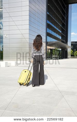 Businesswoman With Yellow Suitcase In Front Of Business Building