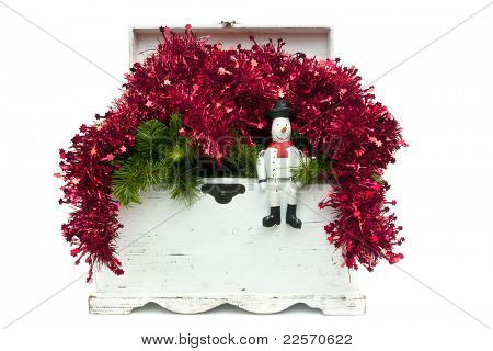 Vintage white wooden chest overflowing with Christmas red tinsel and garlands.  With cute wooden snowman.  Isolated on white.
