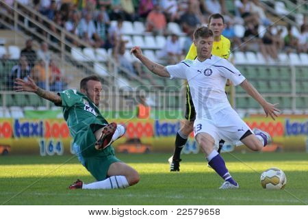 KAPOSVAR, HUNGARY - AUGUST 14: Zoltan Boor (in white) in action at a Hungarian National Championship soccer game - Kaposvar (green) vs Ujpest (white) on August 14, 2011 in Kaposvar, Hungary.