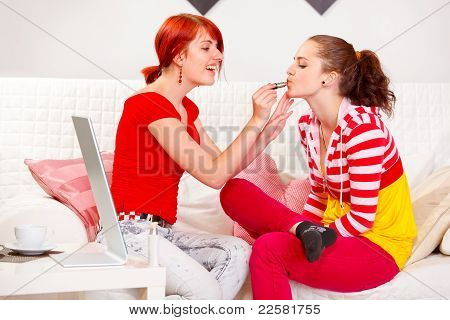 Smiling Girl Applying Lipstick To Her Girlfriend