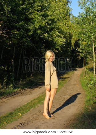 Girl Wolking Away Along The Forest Road