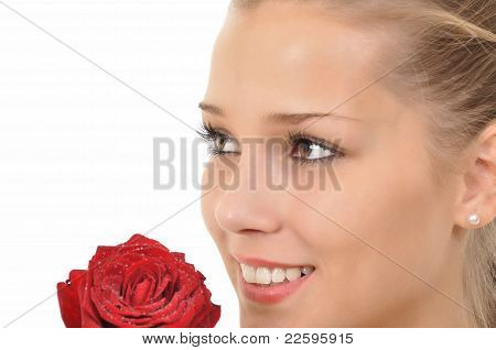 Young woman with rose full of water drops