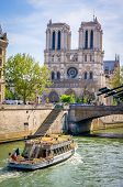 Notre-dame-de-paris Cathedral And A Boat Passing By On The Seine In Paris poster