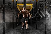 Cross fit training. Man working out with battle ropes at gym  poster