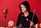 picture of sceptre  - Caucasian witch holds sceptre over red background - JPG