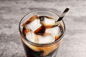 Glass of refreshing cola with ice on table, closeup poster