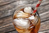 Glass of refreshing cola with ice on wooden background, closeup poster