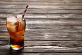 Glass of refreshing cola with ice on wooden background poster