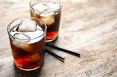Two glasses of refreshing cola with ice on wooden table poster