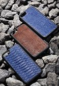 Three Exclusive Brown And Blue Snake Leather Case For Smartphone.luxury Case. On Stone Background poster
