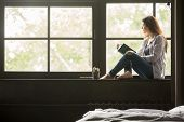 Pensive Dreamy Girl Holding Book Sitting On Sill At Home Looking At Big Window Dreaming, Thoughtful  poster