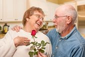Happy Senior Adult Man Giving Red Rose to His Wife Inside Kitchen. poster