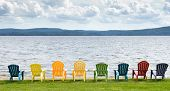 image of lineup  - Eight colorful Adirondack chairs lined up on the beach looking out on the lake - JPG