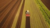 Farmer In Tractor Preparing Land With Seedbed Cultivator In Farmlands. Tractor Plows A Field. Agricu poster