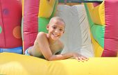 foto of inflatable slide  - A young boy plays in an inflatable slide with water  - JPG