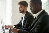 Sneaky Curious Caucasian Businessman Secretly Looking At Laptop Screen Of African Colleague Stealing poster