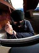 stock photo of scumbag  - robber in a mask opens a window - JPG