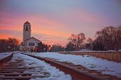 sunrise photo of the boise train depot and the railroad tracks covered in snow with a flock of geese poster