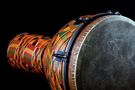 stock photo of congas  - An orange African or Latin Djembe conga drum isolated on black background in the horizontal format with copy space - JPG